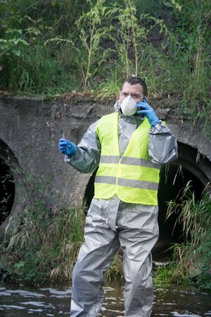 a scientist, wearing a protective suit, blue gloves and a mask, talks on a mobile phone with the management to report the results of the study of the liquid from the river, against the background of a sewer pipe
