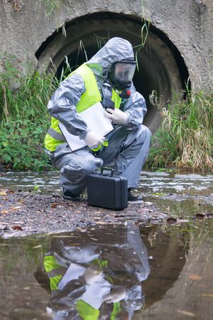 a specialist in a protective suit and mask, on the pond with a suitcase, tablet and mobile phone in his hands, conducts research Stockfoto