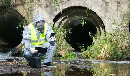 a specialist in a protective suit and mask, on the pond with a suitcase, tablet and mobile phone in his hands, conducts research, against the background of sewer pipes