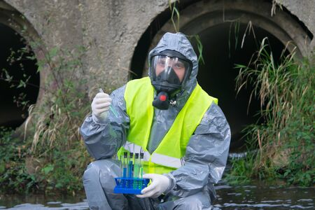specialist in a gray protective suit and mask, on the pond, takes a sample of liquid in test tubes, close-up Stockfoto