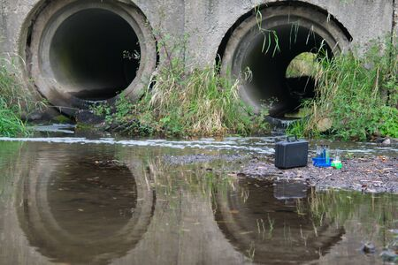 on the background of drainpipes and the river, there are test tubes with liquids and a suitcase for testing in the laboratory
