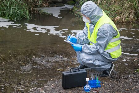 the scientist, wearing a protective suit, gloves and mask, took the liquid from the river, in test tubes, and writes the results in a notebook