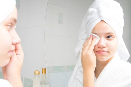girl in a white bathrobe and a towel on her head, near the mirror in the bathroom, cleans her face with a cotton swab