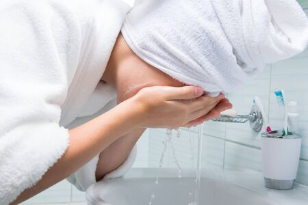 a girl with a white towel on her head and in a dressing gown, in the bathroom, washes foam, for cleansing, from her face, under water from a faucet Stockfoto