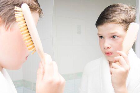 boy, in a white bathrobe, in the bathroom, combing his hair, near the mirror Stockfoto