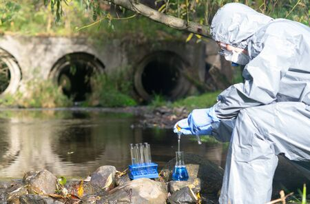 the scientist, in a protective suit and mask, collects water from the river, into test tubes and flasks, there is a place for inscription