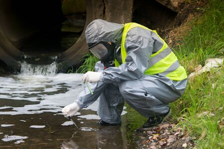 a scientist, in a protective suit, mask and gloves, takes a liquid from the river in test tubes, for a sample, against the background of a drainpipe