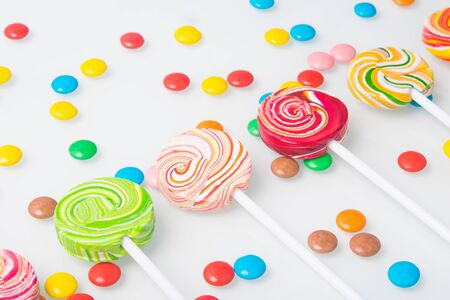 multi-colored lollipops, arranged in a row and round dragees, on a white background