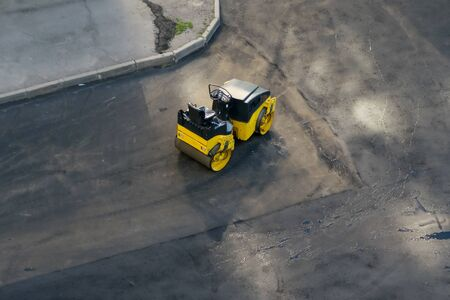 on the background of black asphalt, yellow transport to smooth the road, skating rink, top view