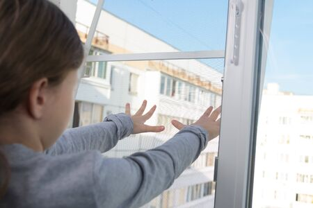 child girl, close-up, pushes the mosquito net out the window, a dangerous situation Stockfoto