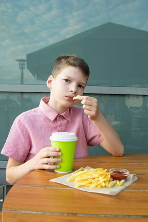 the boy sits at the table eating French fries with ketchup and drink Stockfoto