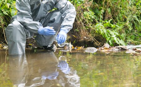 a scientist in a protective suit and blue gloves, conducts research on the ground, holds a glass flask in his hand and takes a sample of water from the river Stockfoto