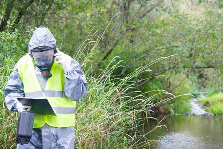 a specialist in a protective suit and mask, with a suitcase and a tablet in his hands, calls on a mobile phone, to report the results of the study to the management, against the background of green nature Stockfoto