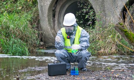 a scientist, in a protective suit and mask, takes the liquid from the river in test tubes, for a sample, against the background of drainpipes