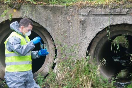 a scientist, in a protective suit, blue gloves and a mask, collects liquid from the river in test tubes, against the background of sewer pipes, there is a place for the inscription