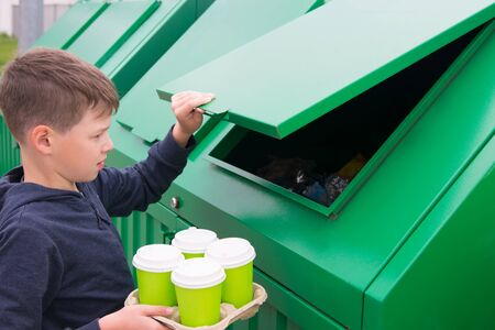 a boy in a blue jumper throws disposable glasses into a green dumpster