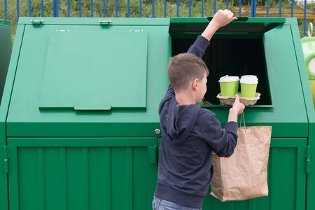 a boy in a blue jumper throws empty disposable glasses and a paper bag into a green dumpster