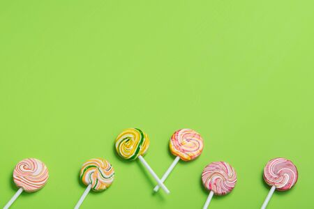 colorful lollipops on a stick, neatly laid out, on a light green background, there is a place for the inscription