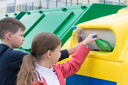 Side view of a boy and a girl throwing trash into a container on the street. Stok Fotoğraf