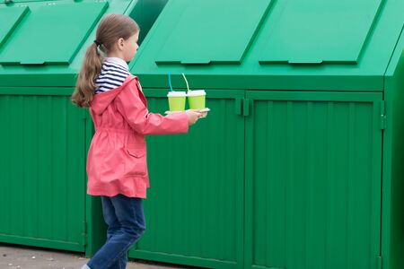 girl throws paper cups into a green trash bin