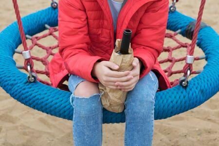 Adolescente en un columpio bebe bebidas ilegales, bebiendo alcohol por niños Foto de archivo