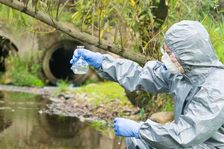 environmental biologist in a protective suit and mask examines water from the river for viruses Banque d'images