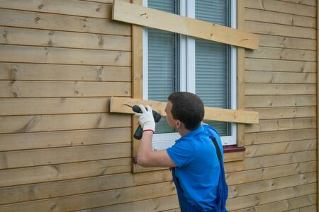 a worker in a blue uniform, drills the window of a wooden house, from thieves, when moving to another address, there is a place for the inscription