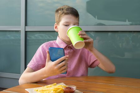 the boy sitting at the table has lunch and looks at the phone, decides his future plans