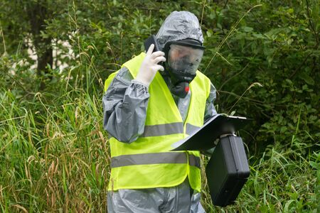 a specialist in a protective suit reports on the phone according to the results of an environmental study looking at the data recorded on a paper tablet