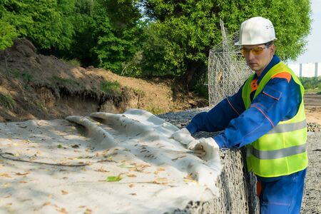 Worker in helmet covers material of a part of the lake landscape