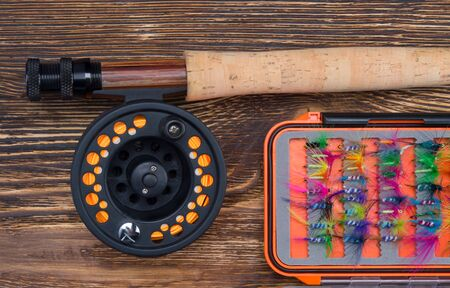composition on a wooden background, a fishing rod with a reel, and a set of bait for fishing