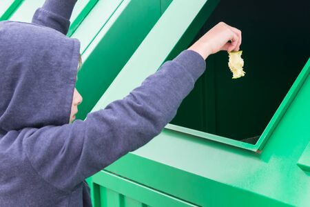 a boy in a hood throws a stub from an apple into a green trash bin 스톡 콘텐츠