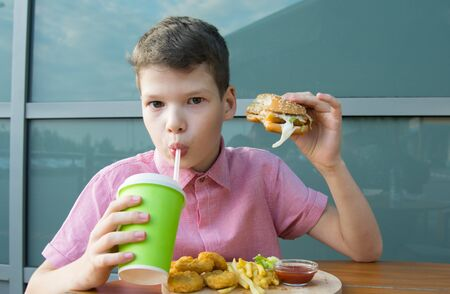 close-up of a boy sitting at a table drinking a drink from a paper Cup with a straw and eating fast food, Burger and nuggets