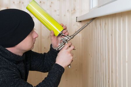 worker in a black hat, makes thermal insulation with mounting foam
