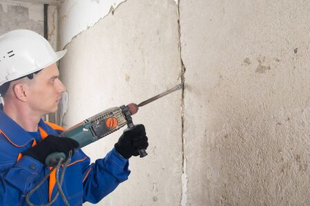 Stripping walls of old concrete, for applying new plaster, using a hammer, workers in protective clothing