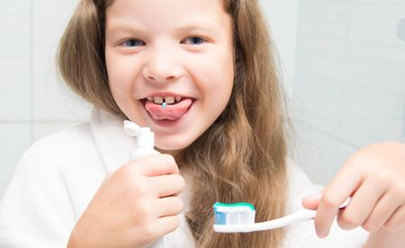 close-up, a girl with long hair, holding a toothbrush in her hand and fooling around, trying to taste the paste Stockfoto