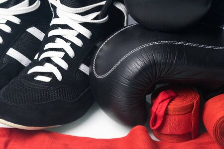 black wrestling gloves, black boxing gloves and unwound red protective bandages for martial arts isolated on a white background, close-up