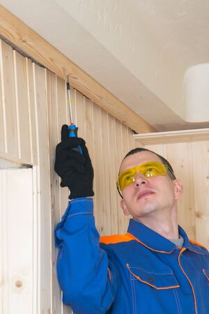 a master in a blue uniform and yellow glasses fixes a wooden beam with a self-tapping screw to insulate the room