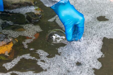 hand in a blue rubber glove pours water from a river into a transparent flask for analysis in a laboratory