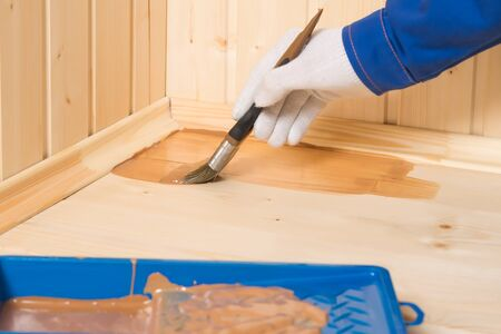 hand with a brush paints a wooden floor with dark impregnation, side view