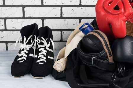 black sports bag with things for training and next to it is wrestling shoes against a brick wall