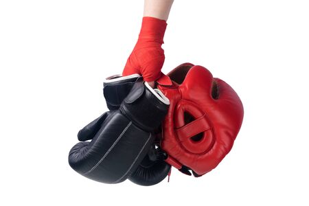athlete's hand holds black gloves and a red safety helmet for boxing isolated on white background
