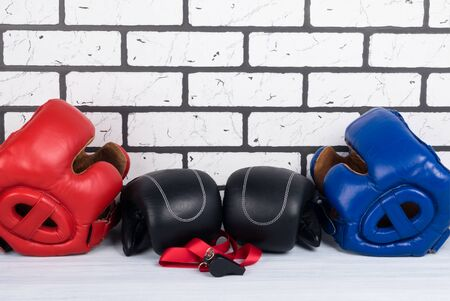 concept of two helmets and gloves for martial arts on a brick wall background