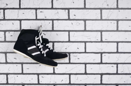 on the background of a brick wall black wrestling shoes, on the right there is a place for inscription Stock Photo