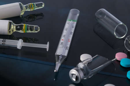 thermometer for measuring temperature and ampoules with medicine lie on x-rays Stock Photo