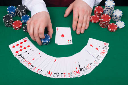 close-up of a green table with cards for playing for money and the hands of a croupier with chips Reklamní fotografie