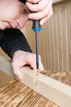 a man holds a wooden block and screws a self-tapping screw into it with a screwdriver