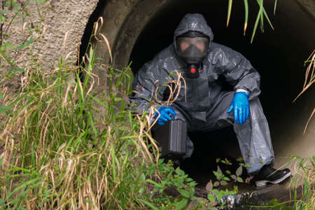 man in protective suit and mask crawls out of the sewer after research, front view Standard-Bild