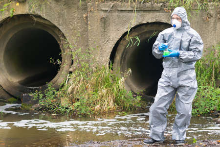 a man in a protective suit and mask looks away holding a flask with express test Standard-Bild