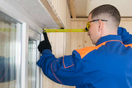 master in blue special clothes measures the thickness of the wall with a tape measure